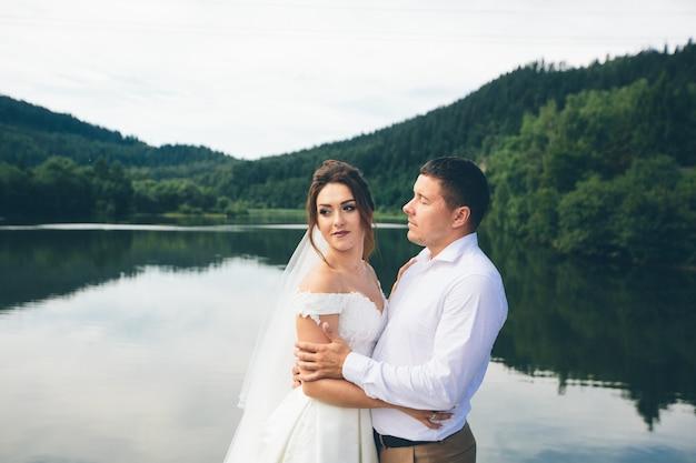 Verliefde paar knuffelen op de achtergrond van een meer in de bergen