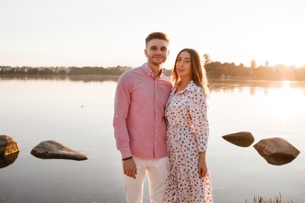 Verliefde paar knuffelen op het meer bij zonsondergang. mooie jonge paar verliefd wandelen aan de oever van het meer bij zonsondergang in de stralen van fel licht. kopieer ruimte