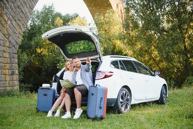 Verliefde paar knuffelen zittend in de kofferbak van de auto kijkend naar de kaart die op reis gaat