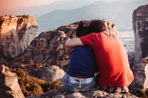 Verliefde paar knuffels op de top van de berg bij zonsondergang, romantiek in meteora, griekenland