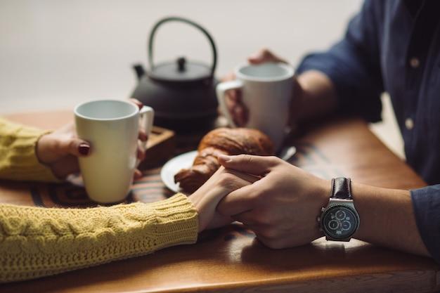 Verliefde paar koffie drinken. handen dicht omhoog