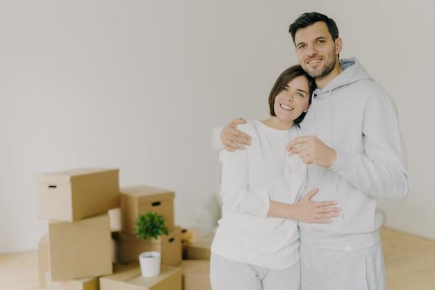 Verliefde paar kopen eigen huis, omhelzen en staan dicht bij elkaar, houden sleutels van nieuw appartement