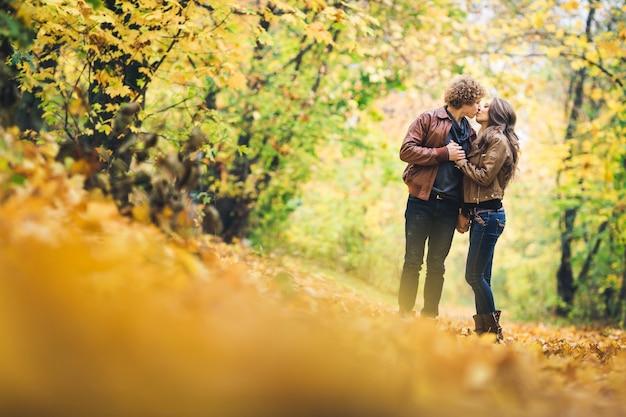 Verliefde paar kussen onder prachtige herfst esdoorns