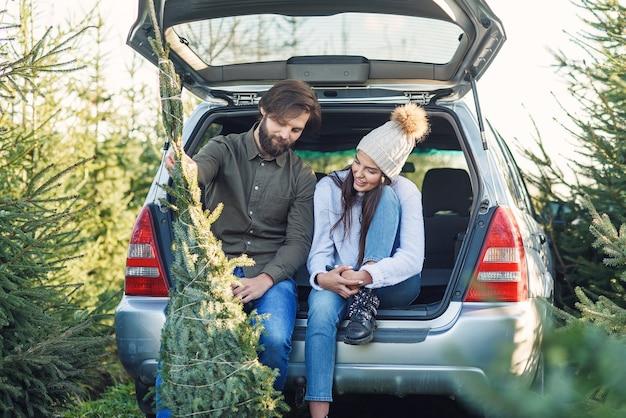 Verliefde paar laden vers gekapte kerstboom in een kofferbak van hun auto. jong gezin voorbereiden op vakantie.