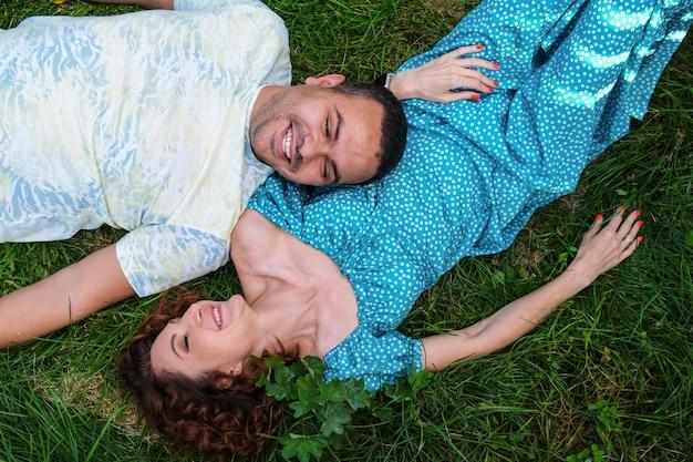 Verliefde paar liggen op het gras, kijken elkaar aan en lachen