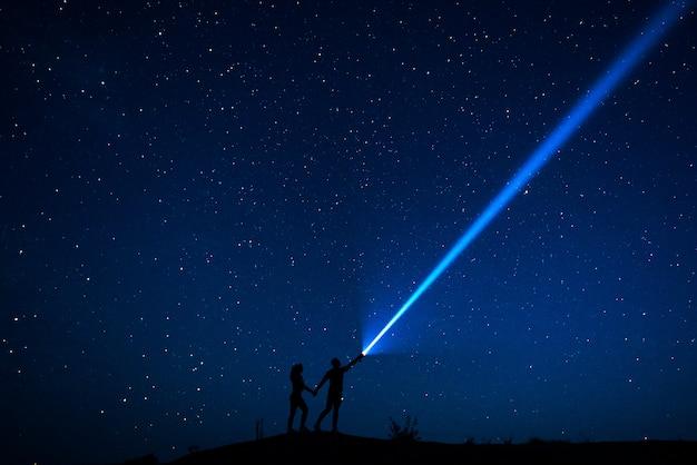 Verliefde paar loopt onder de sterren. silhouet van geliefden paar die genieten van hun tijd samen 's nachts onder een sterrenhemel. sterrenhemel. nachtwandeling. man en vrouw reizen. bruiloft reizen