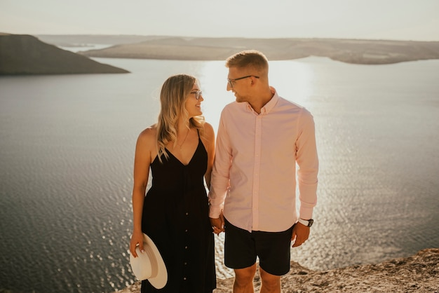 Verliefde paar lopen op een berg boven een groot meer aan zee bij zonsondergang.