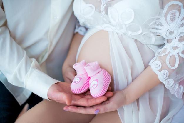 Verliefde paar met babyslofjes voor een meisje op de achtergrond van zwangere buik