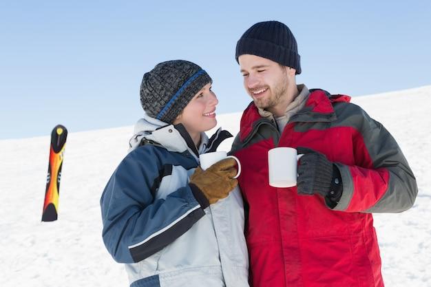 Verliefde paar met koffie met ski-board in de sneeuw