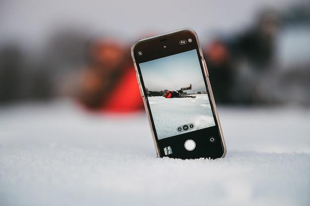 Verliefde paar omarmen en spelen tijdens het nemen van selfie op mobiele telefoon geplaatst op sneeuw op platteland