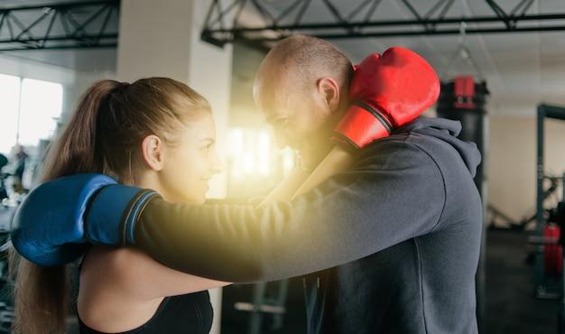 Verliefde paar omhelst in bokshandschoenen en kijkt naar elkaars ogen in de sportschool.