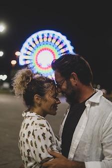 Verliefde paar omhelzen elkaar hartstochtelijk op straat tegen verlicht reuzenrad 's nachts. paar romantiek en quality time buitenshuis doorbrengen tijdens de vakantie 's nachts