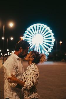 Verliefde paar omhelzen en kussen elkaar hartstochtelijk op straat tegen verlicht reuzenrad 's nachts. paar romantiek en quality time buitenshuis doorbrengen tijdens de vakantie 's nachts