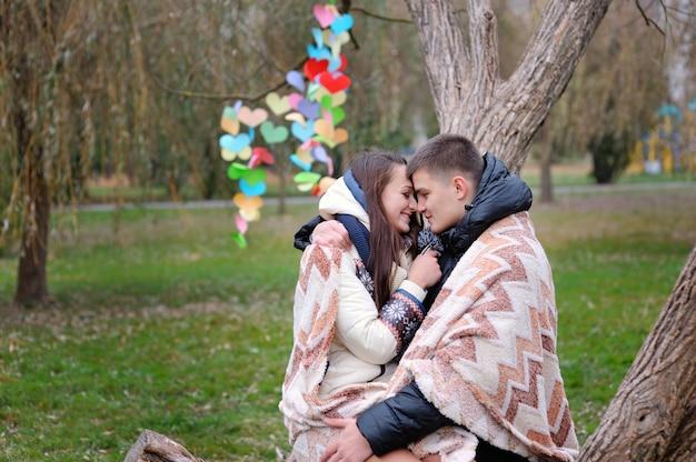 Verliefde paar onder deken is verwarmd herfst park