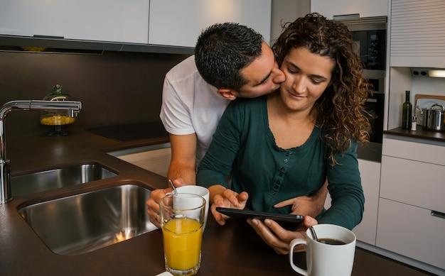 Verliefde paar ontbijten in de keuken en kijken naar de tablet