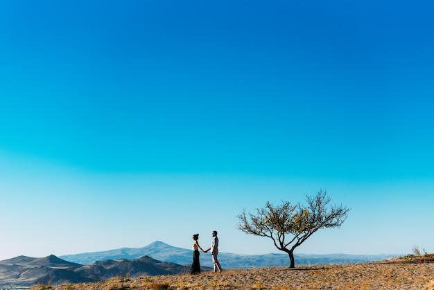 Verliefde paar ontmoet zonsondergang in de bergen. echtpaar reist. liefhebbers in de natuur. man en vrouw die op de zonsondergang letten. liefhebbers bij zonsondergang. reis in de bergen. man en vrouw hand in hand