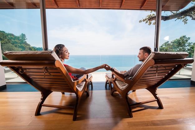 Verliefde paar ontspannen op de ligbedden en kijken elkaar hand in hand op het terras van hun luxe villa. prachtig zeezicht