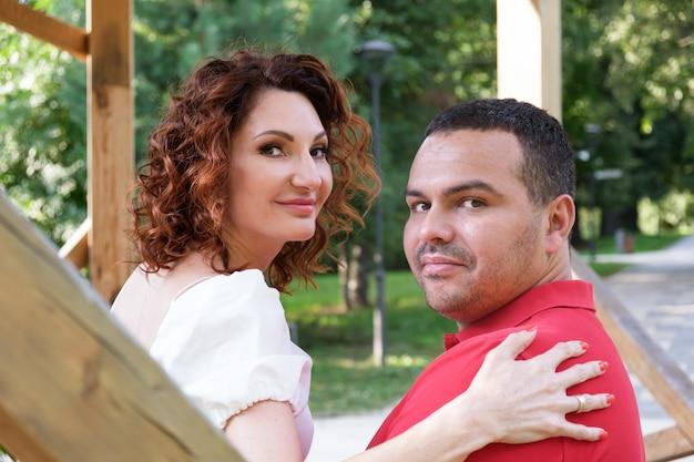 Verliefde paar op bankje in het park draaide zich om en keek naar de camera. romantische zomerwandeling