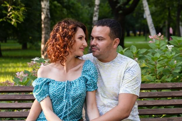 Verliefde paar op een bankje in het park kijken elkaar teder aan
