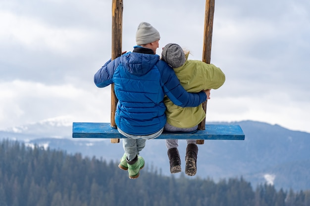 Verliefde paar op een schommel in de bergen van de winter. relatie, vakantie, reisconcept