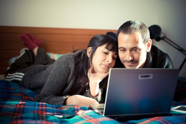Verliefde paar op het bed met behulp van laptop