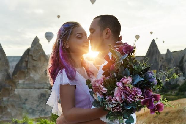 Verliefde paar op landschap met ballonnen