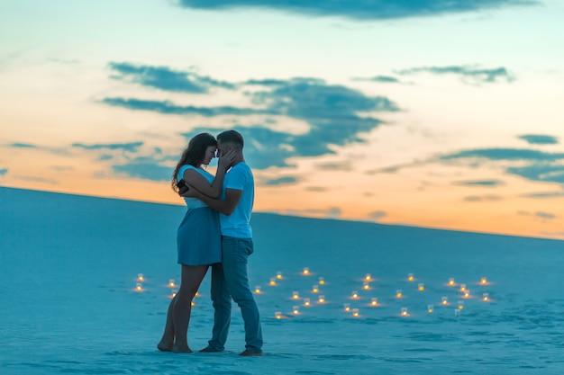 Verliefde paar romantische knuffels in zandwoestijn, avond, romantische sfeer, in zand branden kaarsen