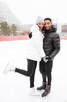 Verliefde paar schaatsen op de ijsbaan buitenshuis.