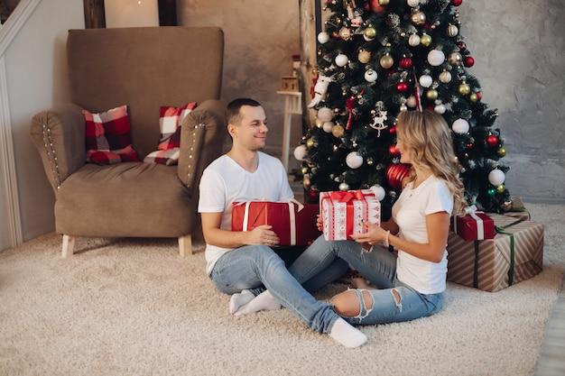 Verliefde paar sorteren presenteert door kerstboom