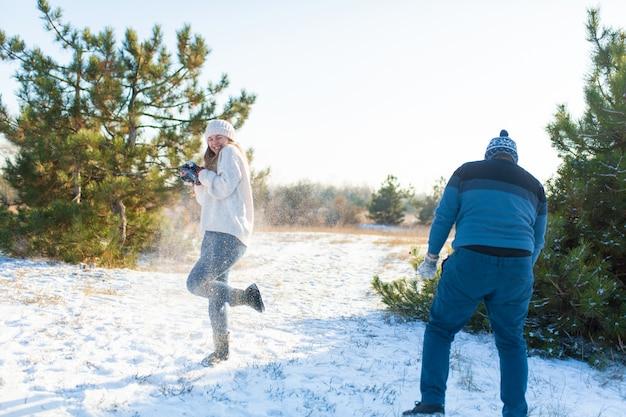 Verliefde paar spelen sneeuwballen in de winter in het bos