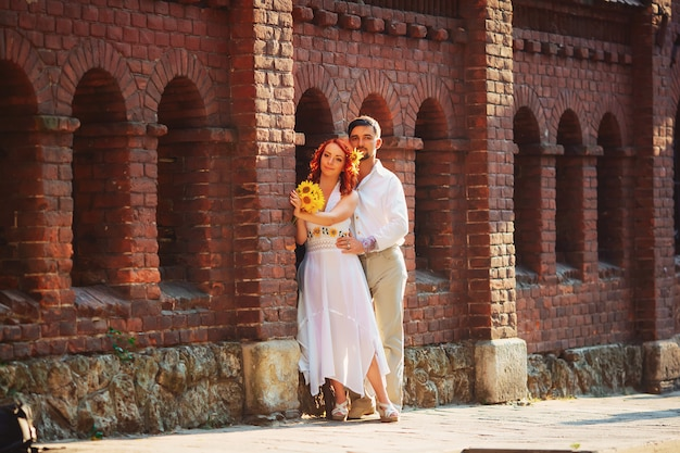 Verliefde paar staande en knuffelen op een oranje muur en hun schaduw valt op de vloer