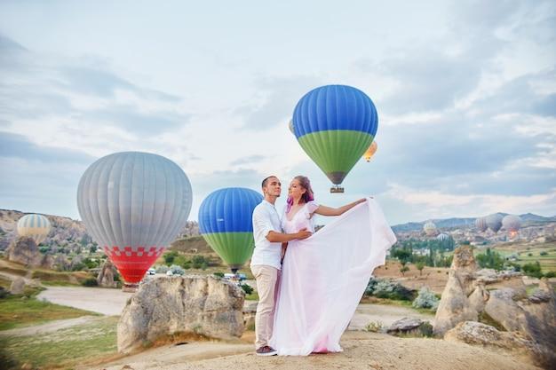 Verliefde paar staat met ballonnen in cappadocië.