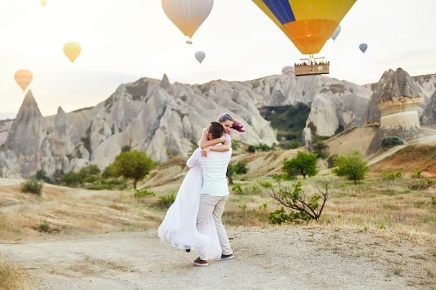 Verliefde paar staat op de achtergrond van ballonnen in cappadocië. man en vrouw op heuvel kijken naar een groot aantal vliegende ballonnen. turkije cappadocia fairytale landschap van bergen. bruiloft op de natuur
