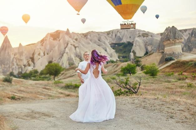 Verliefde paar staat op de achtergrond van ballonnen in cappadocië