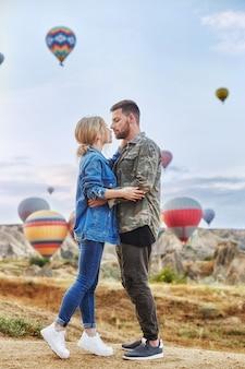 Verliefde paar staat op de achtergrond van ballonnen in cappadocië.