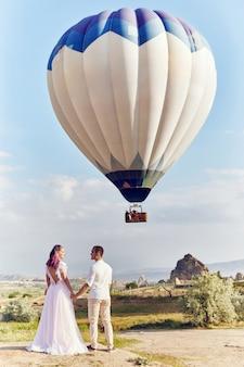 Verliefde paar staat op landschap met ballonnen