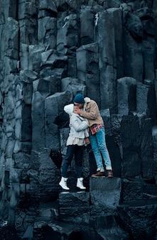 Verliefde paar toeristen staan hand in hand en kussen op de stenen van zwarte vulkanische basaltbergen. reizen, recreatie, toerisme.