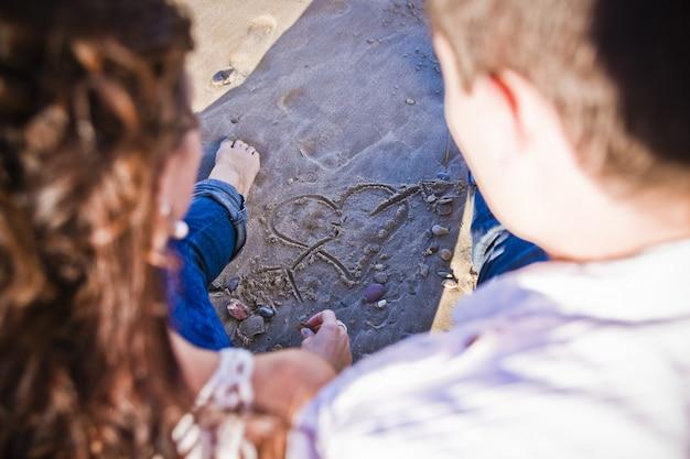 Verliefde paar trekkend een hart in het zand op de stranddagen vóór hun scheiding en scheiding.