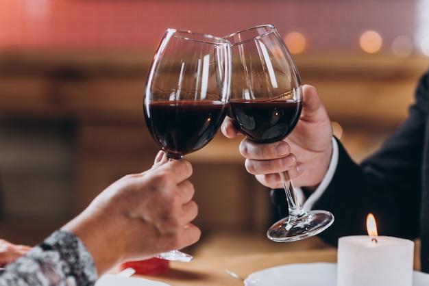 Verliefde paar verhoogt glazen rode wijn