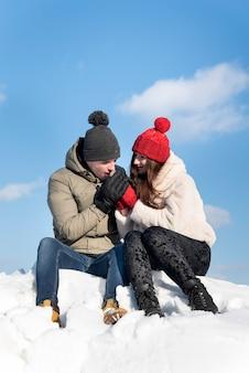 Verliefde paar zit op sneeuw tegen blauwe hemel. guy verwarmt de handen van zijn geliefde.