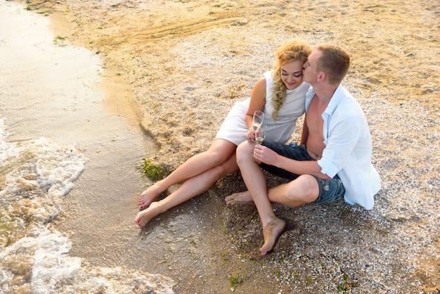 Verliefde paar zit 's avonds op het strand en drinkt champagne