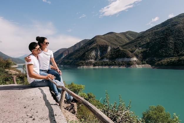 Verliefde paar zitten en kijken naar een prachtig uitzicht op het zhinvalskoe reservoir, georgia.