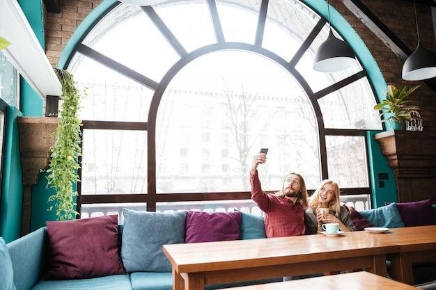 Verliefde paar zitten in café en praten terwijl selfie maken.