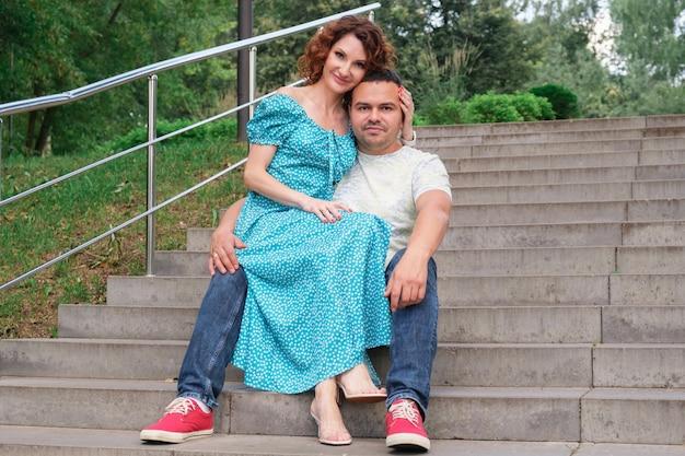 Verliefde paar zitten op de trap in het park en omhelzen elkaar teder