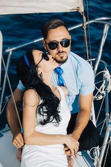 Verliefde paar zitten op het dek van het jacht, omhelzen elkaar.