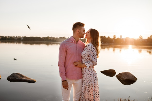 Verliefde paar zoenen op het meer bij zonsondergang. mooie jonge paar verliefd wandelen aan de oever van het meer bij zonsondergang in de stralen van fel licht. kopieer ruimte