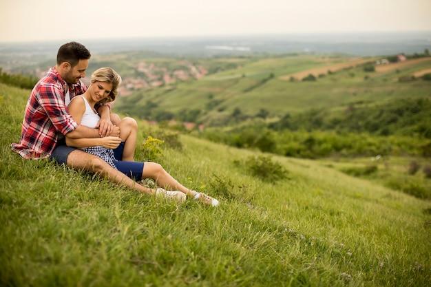 Verliefde paarzitting die op gras in de berg wordt gekoesterd