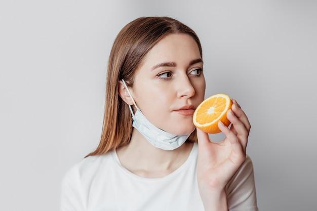 Verlies van geur concept. portret van een blanke jonge vrouw met een sinaasappel in de buurt van haar neus geïsoleerd