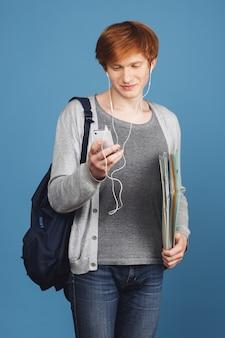 Verlies van jonge aantrekkelijke roodharige mannelijke student in casual grijze outfit met zwarte rugzak die notebooks in handen houdt, oortelefoons draagt, lied kiest om te luisteren op smartphone
