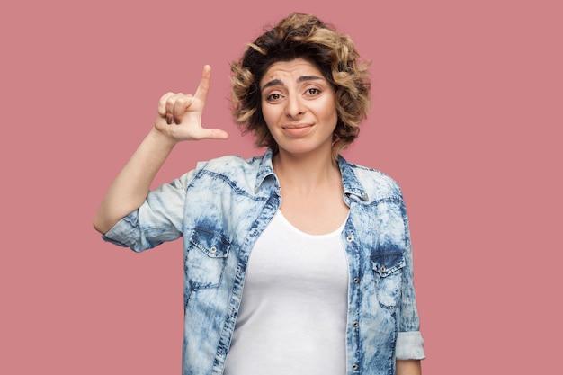 Verliezer. portret van een trieste jonge vrouw met krullend kapsel in een casual blauw shirt dat met een verliezersgebaar staat en naar de camera kijkt met een mislukt gezicht. indoor studio opname, geïsoleerd op roze achtergrond.